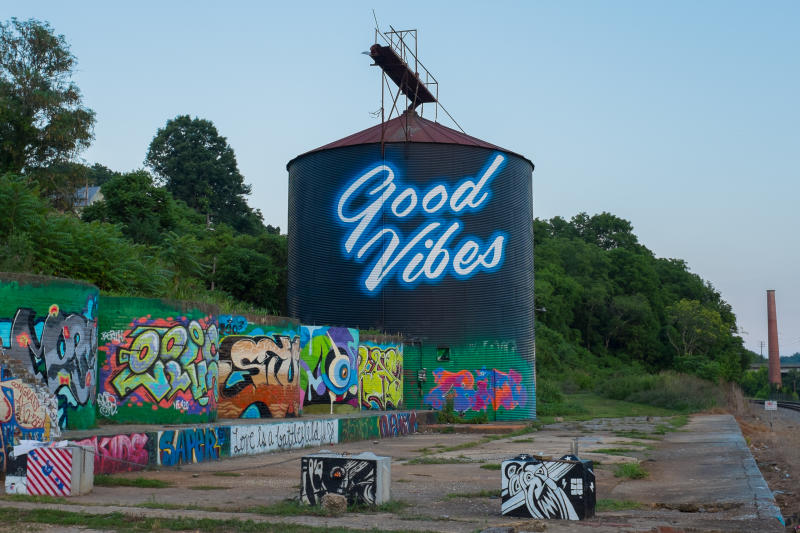 "A Water Tower with the words ""good vibes"" and graffiti expressing the Arts Scene"