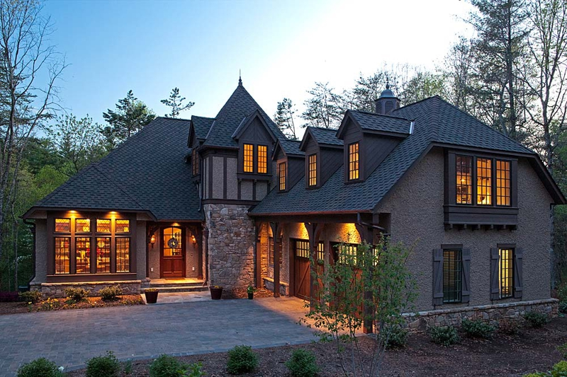 photo of a stone mansion taken at dusk with golden yellow light coming though the windows