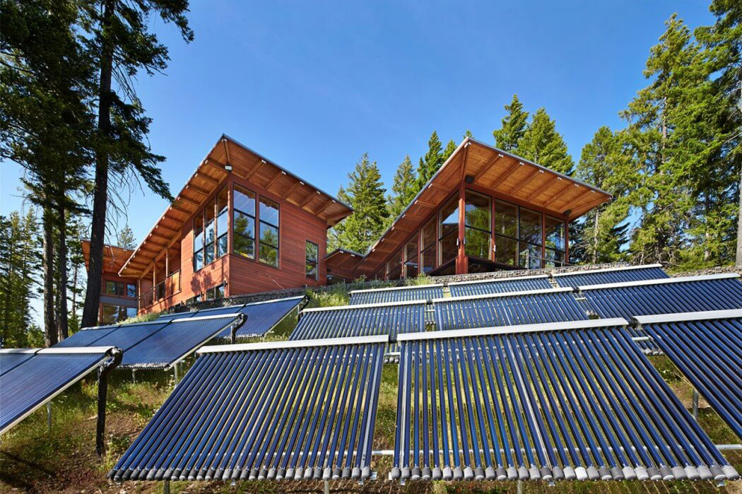cabin style mansion in a forest with solar panels in front of it