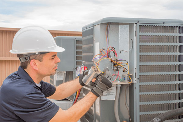 young HVAC worker repairing wires on an ac unit outdoors
